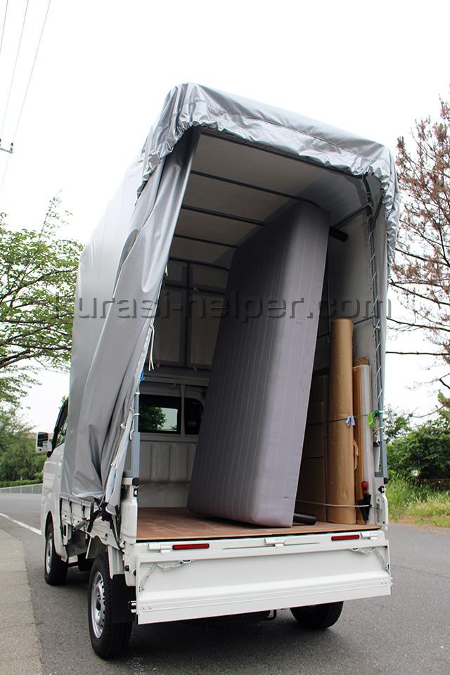 ベッドマットを立てて積むことができる幌付きの軽トラック