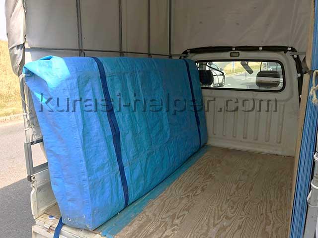 ベッドマットをカバーで包み、横にして軽トラックの荷台に積んだ様子