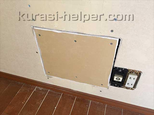 壁紙を剥がし、穴を板でふさいでいる様子