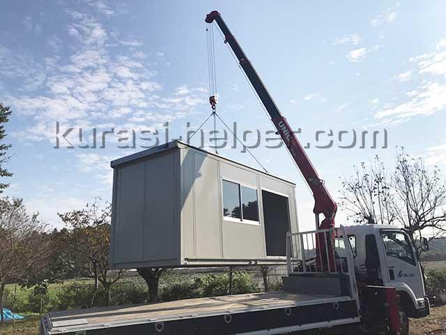 建て替え中に荷物を保管するためのコンテナボックスをクレーンを使って設置