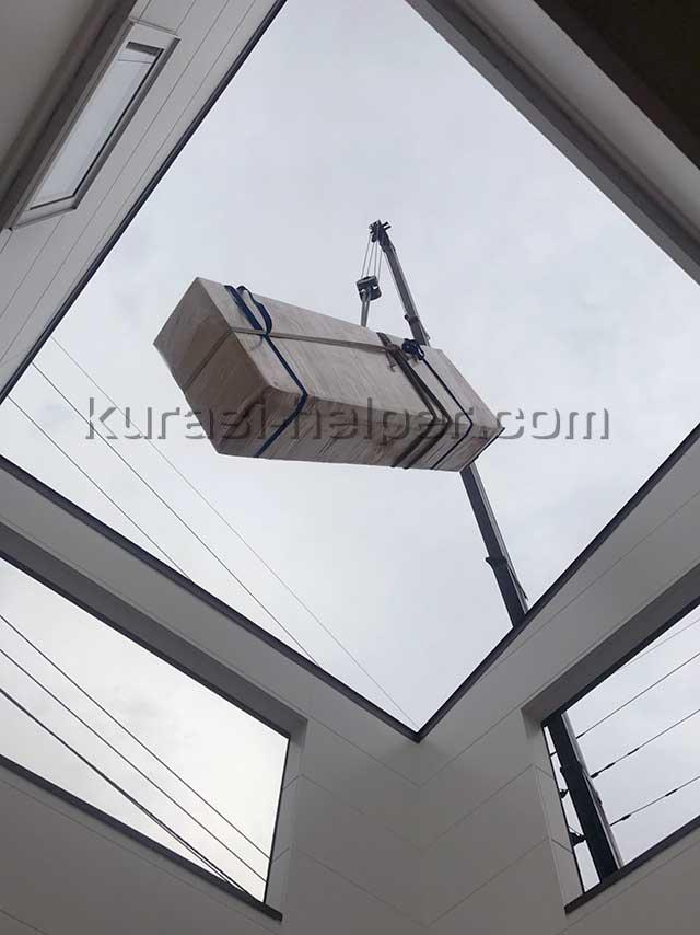 クレーンで吊り上げた家具を吹き抜けに下ろしている様子