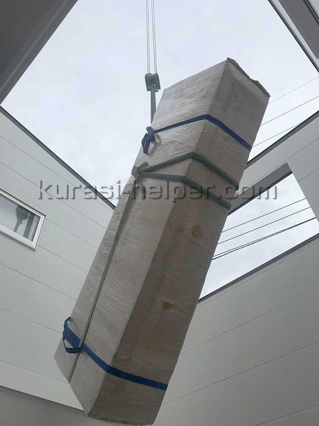 クレーンで吊り上げた家具を吹き抜けの上から下ろした様子